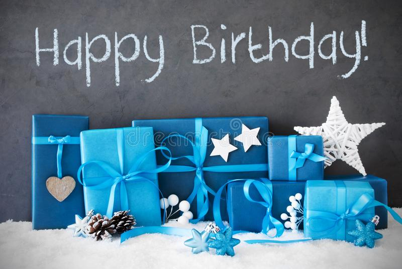 Christmas Gifts, Snow, Text Happy Birthday. Concrete Wall With English Text Happy Birthday. Blue Christmas Gifts With Decoration Like Stars And Fir Cone On Snow stock photos