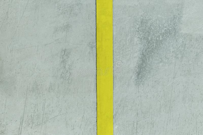 Concrete wall. filmed in dark weather. it has a strip of yellow color. divided into two parts.  royalty free stock photo