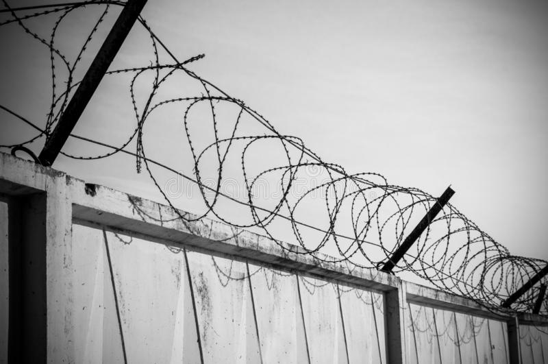 Concrete wall with razor barbed tape wire on blue sky background on a Sunny day stock photo