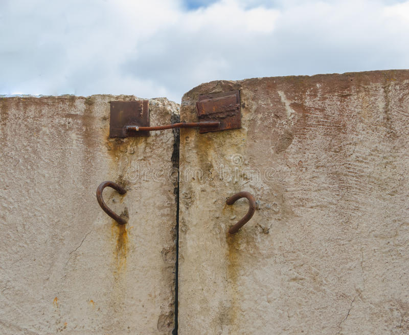 Concrete wall sticking out of it's rusty hinges for transportation. Old rusty hinges sticking out and cement walls royalty free stock images