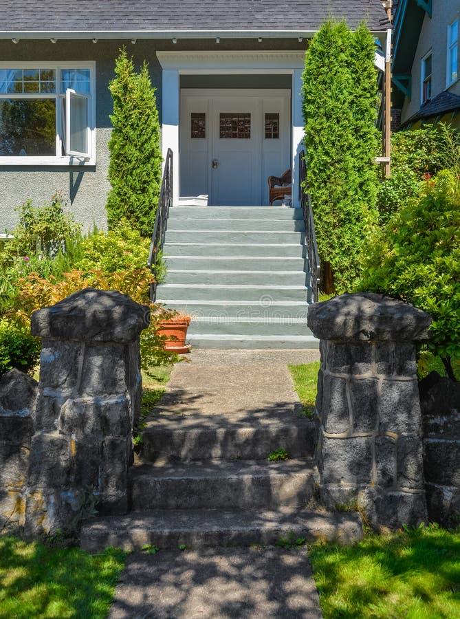 Concrete weg aan woonhuisingang via gemodelleerde vooryard stock fotografie