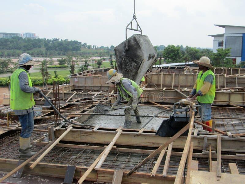 Concreting工作在工地工作的建筑工人旁边 免版税库存照片