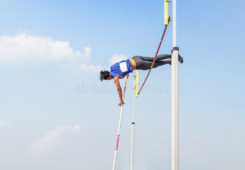 Concurrence de sauter de poteau de chambre forte de poteau d'athlète au-dessus de barre dedans au ciel photo libre de droits