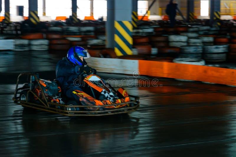 Concurrence karting dynamique à la vitesse avec le mouvement trouble sur une piste équipée image stock
