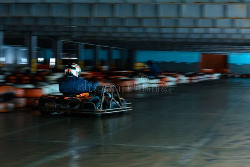 Concurrence karting dynamique à la vitesse avec le mouvement trouble sur une piste équipée photos libres de droits