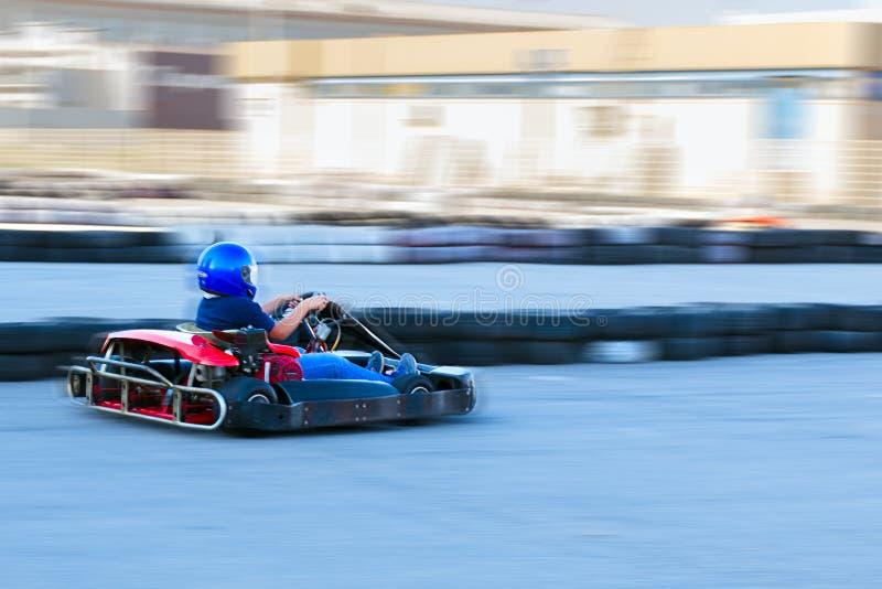 Concurrence karting - le conducteur en forme protectrice à la vitesse passe le cercle de la trace de kart photos stock
