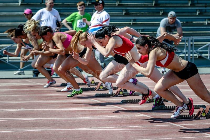 Concurrenten op begin van 100 m-vrouwen royalty-vrije stock afbeelding