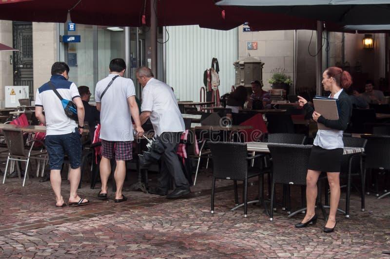 Concurrentie tussen twee werkgevers die de klant in terrassenrestaurant in stad willen aantrekken stock foto