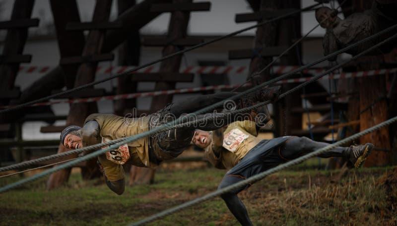 Concurrents tombant des cordes à la course 2014 d'obstacle de gars dur image stock