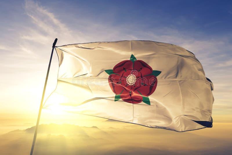 Condado de Lancashire da tela de pano de matéria têxtil da bandeira de Inglaterra que acena na névoa superior da névoa do nascer  ilustração royalty free