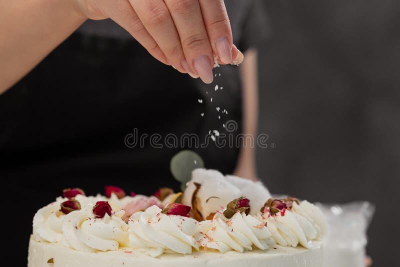 Condater kropi tort z kraciastymi migdałami i koksem W górę ręki i dolewanie kruszek obraz royalty free