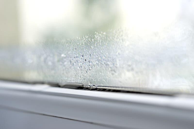 Condensación en la doble vidriera del primer de las ventanas de cristal del pvc imagenes de archivo