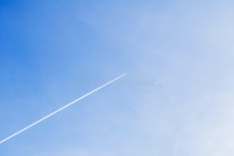 Condensatiespoor die van vliegtuig hoog tegen in duidelijke blauwe hemel vliegen Met plaats voor uw tekst voor moderne achtergron stock afbeeldingen