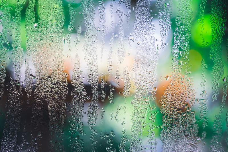 Condensation on the clear glass window with colorful background. Water drops. Rain. Abstract background texture royalty free stock image