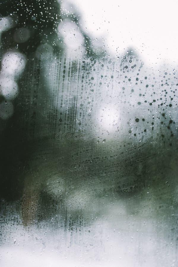Condensation et gouttes de pluie fraîches contre une fenêtre d'une voiture photo stock