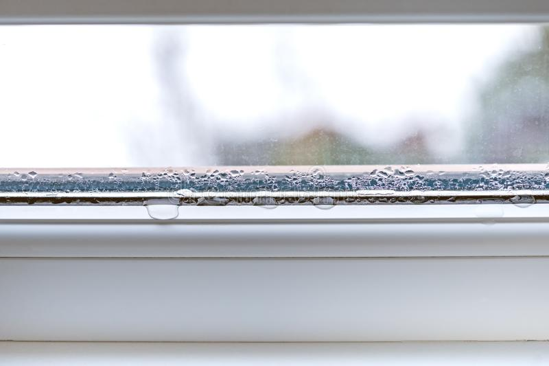 Condensation sur le double vitrage de plan rapproché de fenêtres en verre de PVC images stock