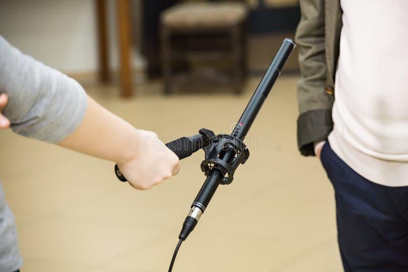 Condensatorshotgun-microfoon Een vrouw interviewt een man De microfoon in de hand van de verslaggever stock foto's