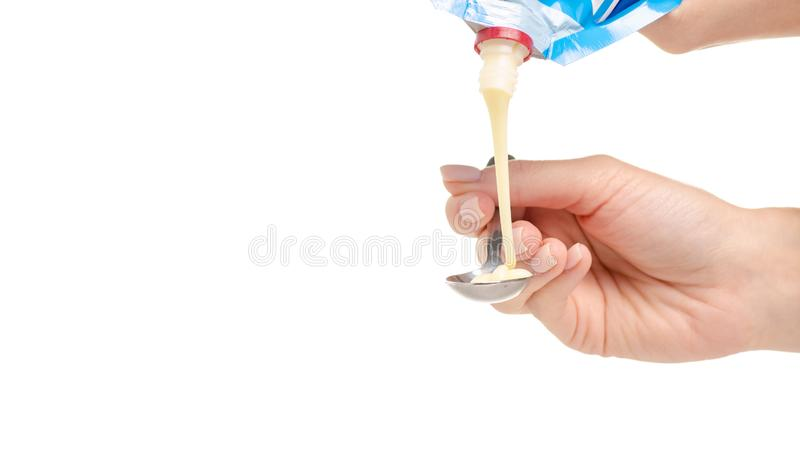 Condensed milk in spoon in hand stock images