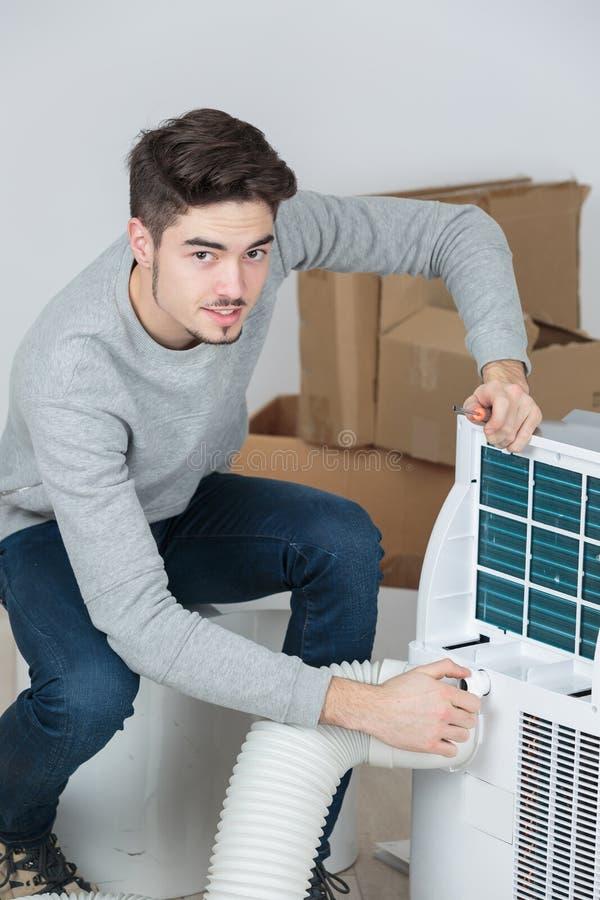 Condicionador de ar sujo do filtro da manutenção da limpeza do homem novo foto de stock