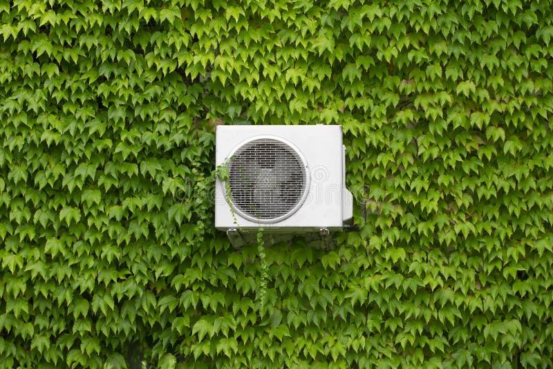 Condicionamento de ar cinzento em uma parede coberto de vegetação com as folhas verdes imagens de stock royalty free
