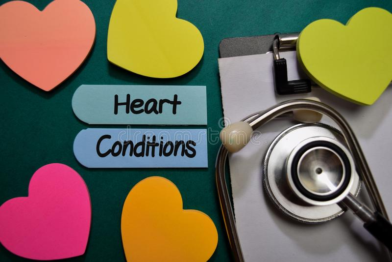 Condiciones cardíacas escribir en una nota adhesiva aislada en Office Desk Atención médica o concepto médico foto de archivo libre de regalías