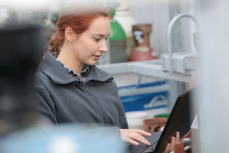 Condifent żeński pracownik fabryczny używa laptop zdjęcia royalty free