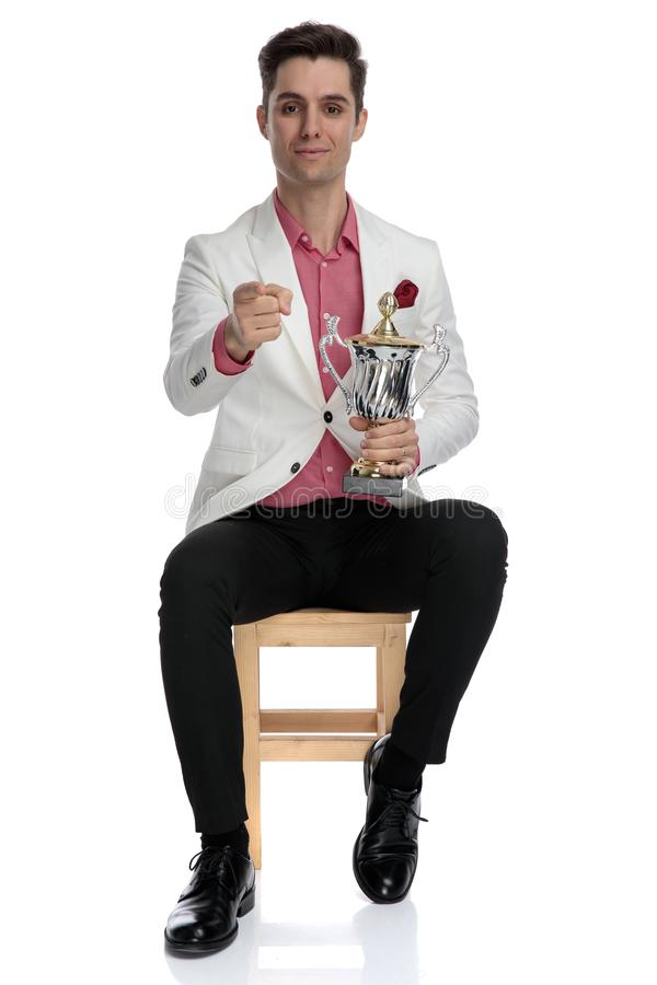 Condifent seated elegant man holding trophy and pointing finger stock photo