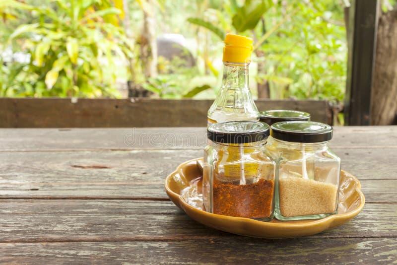 Condiment установил с порошком и желтым сахарным песком chili с соусом рыб на керамическом подносе на деревянном столе над запачк стоковое фото