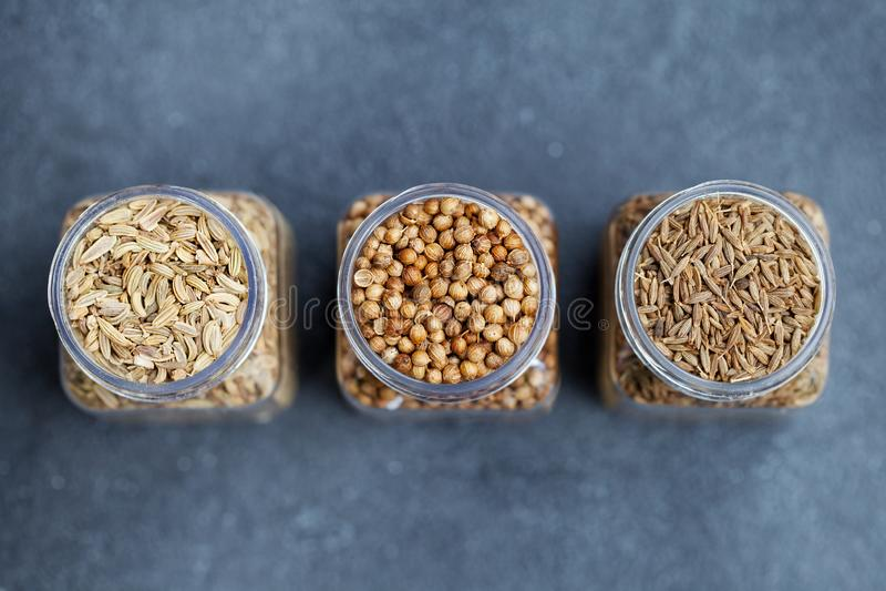 Condimenta el surtido en tarros, hinojo, coriandro, semilla de comino Fondo de piedra gris Visi?n superior Copie el espacio imagen de archivo