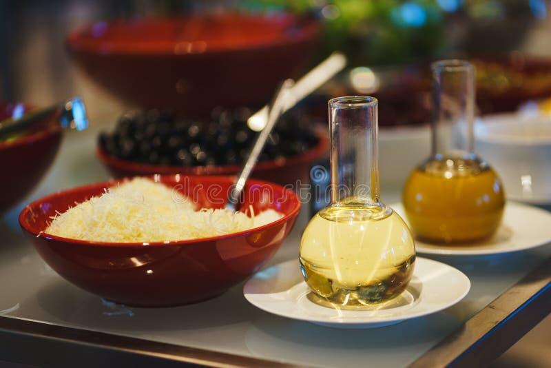Condimento degli ortaggi freschi, delle erbe, delle olive, della salsa e dell'insalata al contatore fotografia stock libera da diritti