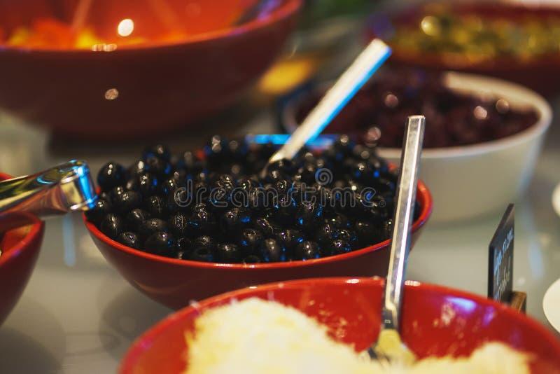 Condimento degli ortaggi freschi, delle erbe, delle olive, della salsa e dell'insalata al contatore immagine stock