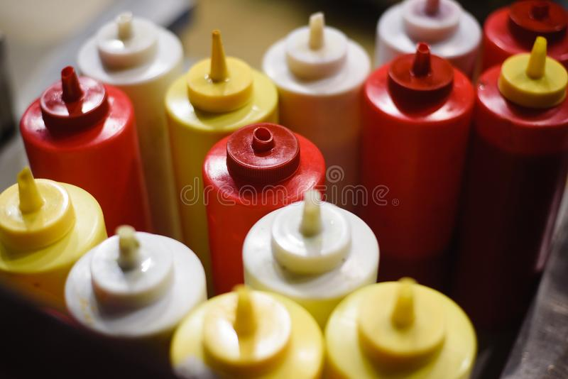 Condimentos da mostarda, da maionese, da ketchup e do molho picante em um carro do cachorro quente para seu uso fotos de stock