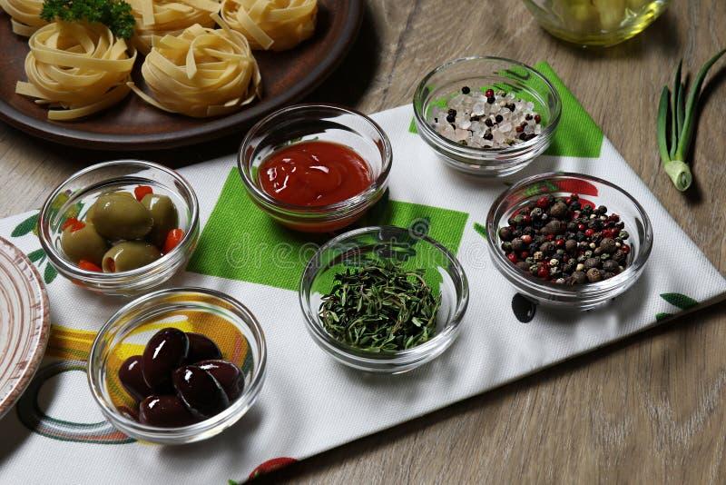 Condimentos para los platos, aceitunas, aceitunas, salsa de tomate, albahaca, opinión superior sobre el fondo de una placa con ta fotografía de archivo
