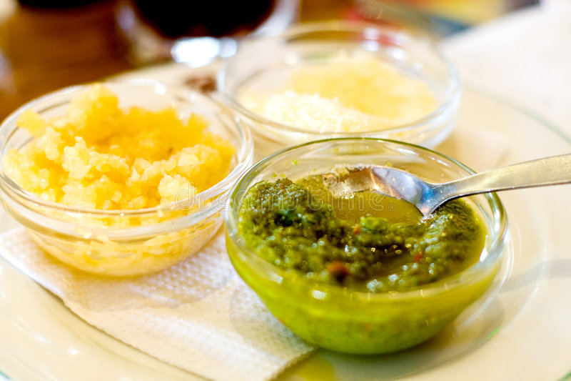 Condiments. 3 bowls of italian condiments - garlic, cheese, and chilli in olive oil royalty free stock photos