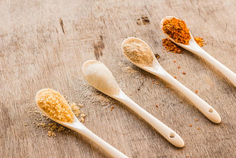 Condiments in spoon. And on old table royalty free stock photo