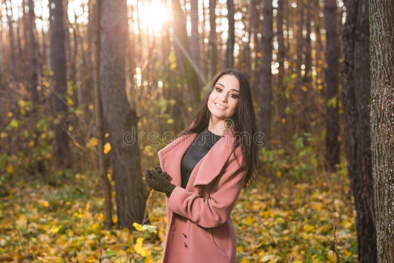 Condisca, caduta e concetto della gente - bella giovane donna che cammina nel parco di autunno immagine stock