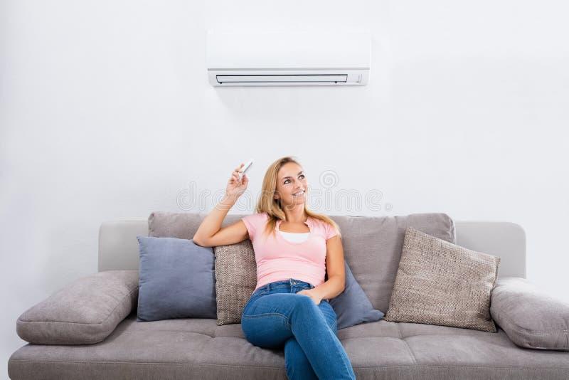 Condizionatore d'aria di funzionamento della donna con telecomando immagini stock