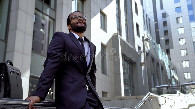 Condizione afroamericana degli impiegati sulle scale vicino all'edificio per uffici, prospettive immagine stock libera da diritti