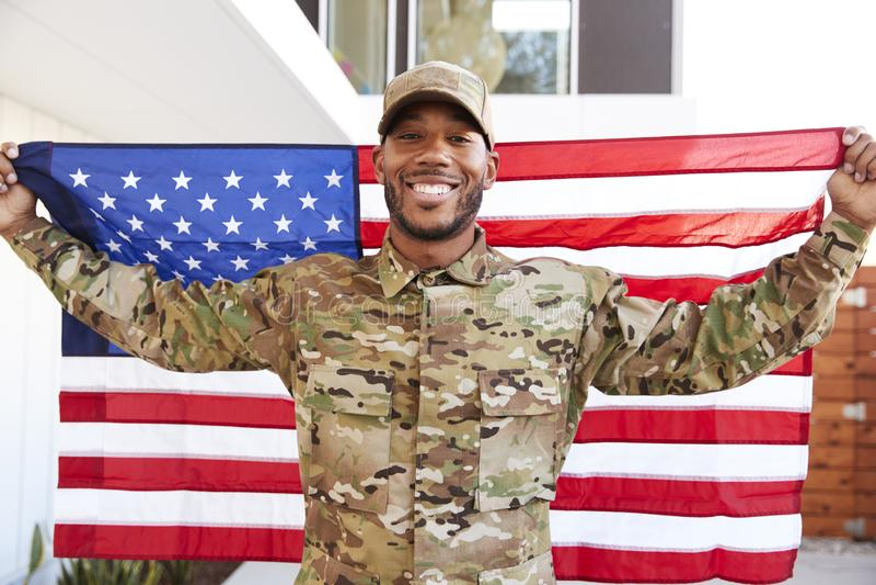 Condizione afroamericana millenaria del soldato fuori della costruzione moderna che tiene la bandiera degli Stati Uniti, sorriden fotografia stock
