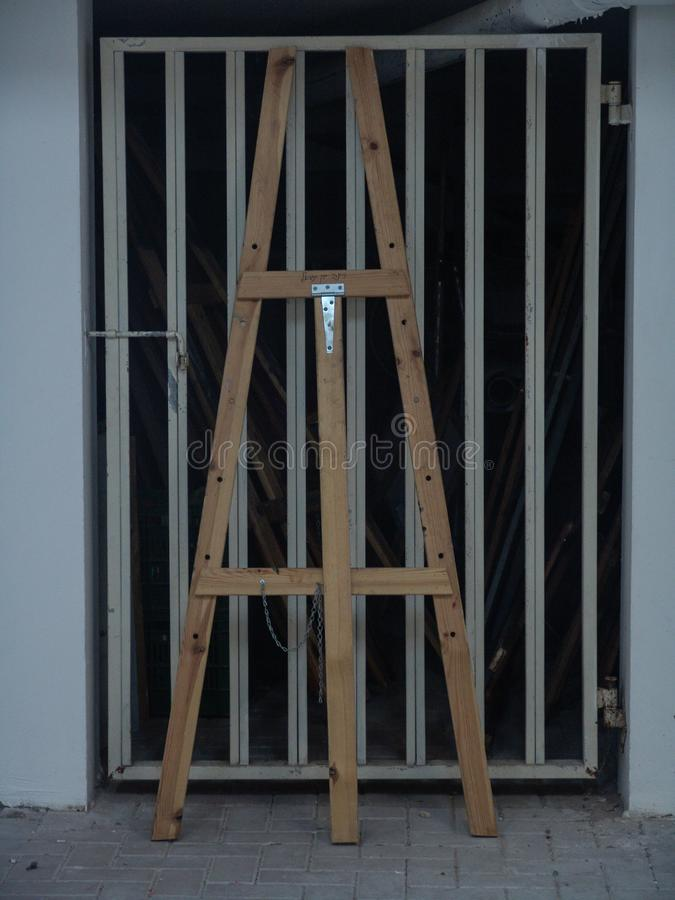 Condizione alta di legno del cavalletto contro una porta del garage del metallo nel bianco immagine stock