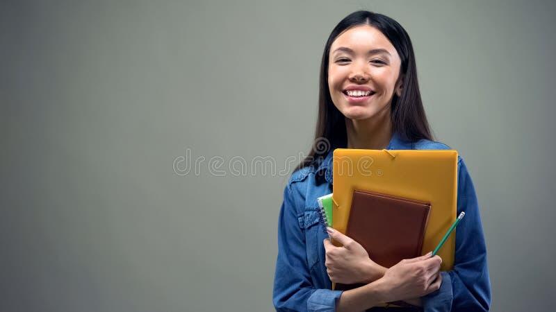 Condizione asiatica della donna con i quaderni su fondo grigio, corsi di gestione fotografia stock libera da diritti