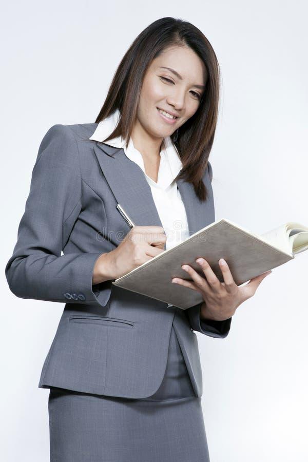 Condizione attraente asiatica della donna di affari facendo uso di una penna che scrive diametro immagine stock