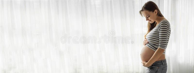 Condizione attraente felice della donna incinta vicino alla finestra e tenere la sua pancia immagine stock libera da diritti