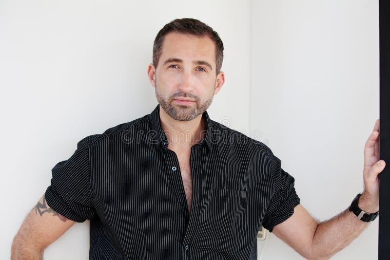 Condizione barbuta bella dell'uomo con la camicia nera aperta immagine stock libera da diritti