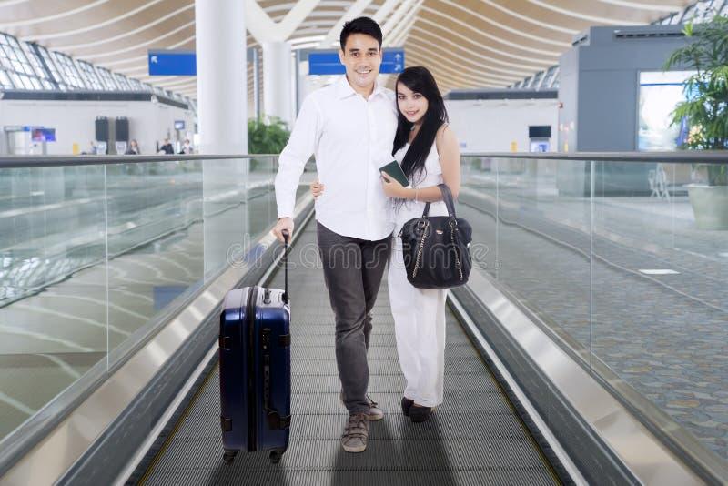 Condizione bianca d'uso delle coppie felici su un tappeto mobile dell'aeroporto fotografia stock libera da diritti