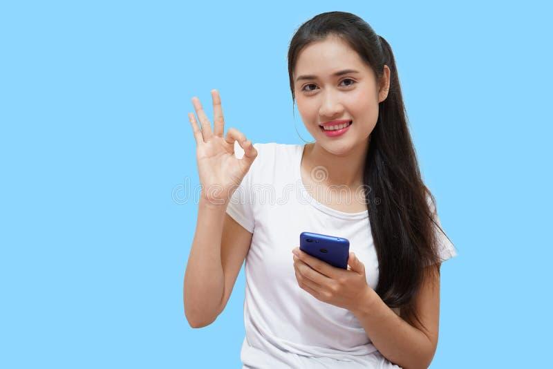 Condizione bianca d'uso tailandese della maglietta delle donne felici della giovane signora del ritratto isolata sopra fondo gial immagine stock libera da diritti