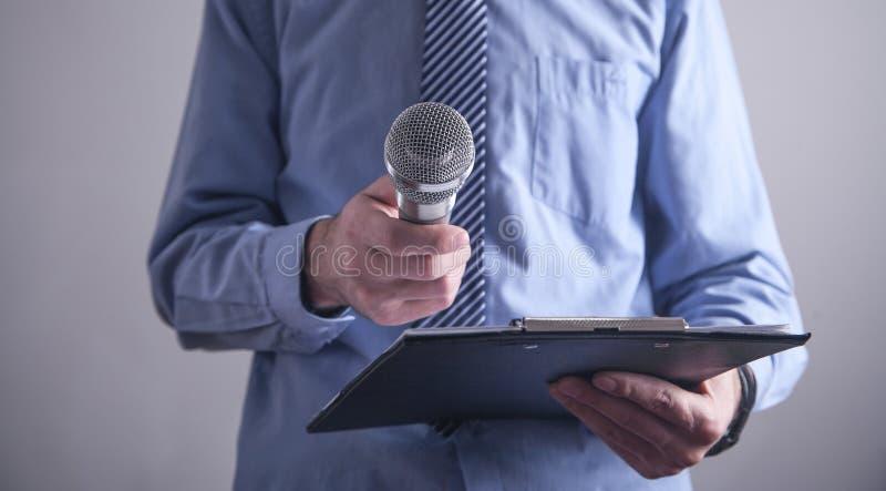 Condizione caucasica dell'uomo d'affari in microfono della tenuta dell'ufficio fotografia stock