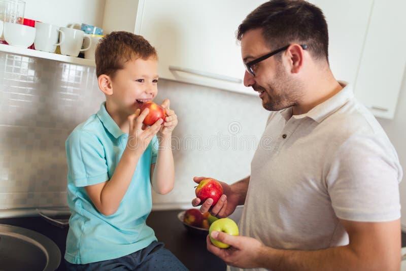 Condizione del bambino e del padre nella cucina nell'abbraccio Essi che tengono frutta in mani fotografia stock