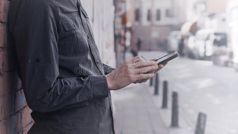 Condizione del giovane contro un fondo della parete e uno smartphone usando fotografia stock