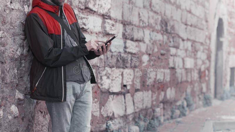 Condizione del giovane contro un fondo della parete e uno smartphone usando fotografia stock libera da diritti